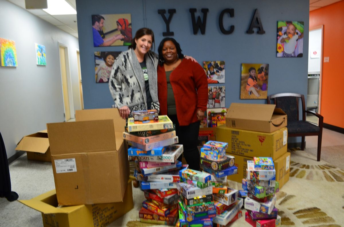 Kate the owner of Gingerbread House Toys standing behind boxes of puzzles donated to the YWCA